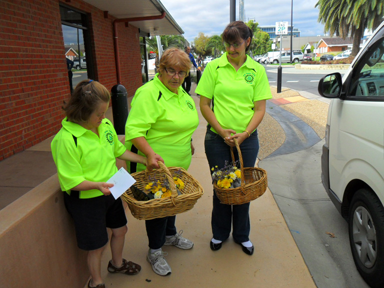 Three women wearing flurscent Murray Valley Centre shirts are pictured carry baskets of flowers. They are on their way to deliver them to customers of the Flower Power Program